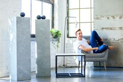 Молодой красивый человек ослабляя в кресле в стиле apar просторной квартиры стоковые фото