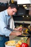 Молодой красивый человек подготавливая обед стоковые фотографии rf