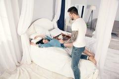 Молодой, красивый молодой человек принес круассаны и кофе на завтрак в кровати к его любимой девушке стоковое изображение rf