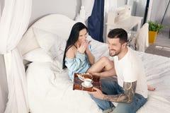 Молодой, красивый молодой человек принес круассаны и кофе на завтрак в кровати к его любимой девушке стоковое фото rf