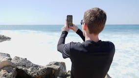 Молодой красивый человек принимая изображения океана и волн ударяя скалистый пляж с брызгать воду на солнечный ветреный день clos видеоматериал
