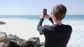 Молодой красивый человек принимая изображения океана и волн ударяя скалистый пляж с брызгать воду на солнечный ветреный день r сток-видео