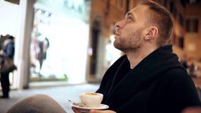 Молодой красивый человек сидя в кафе в вечере и выпивая кофе, тратя время в центре города сток-видео