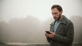 Молодой красивый человек стоя в самом начале туманное утро в парке Бородатый мужчина используя smartphone с сенсорным экраном сток-видео