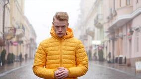Молодой, красивый человек стоя на дороге и свирепо смотря камеру, улицу на предпосылке сток-видео
