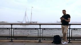 Молодой красивый человек стоя на пристани около загородки и используя smartphone около воды, просматривая интернет видеоматериал