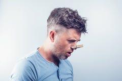 Молодой красивый человек с зажимкой для белья на его носе аллергически стоковая фотография rf