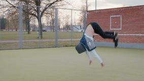 Молодой, красивый, энергичный парень, танцор улицы в черных брюках и голубой жилет с клобуком, выполняя циркаческое сток-видео