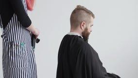Молодой красный с волосами женский парикмахер режет волосы бородатого клиента человека акции видеоматериалы