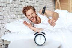 Молодой красный с волосами человек бьет будильник молотком стоковое изображение rf