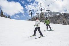 Молодой лыжник и катание на лыжах и восхождение на борт snowboarder вниз с лыжи склоняют Стоковая Фотография RF