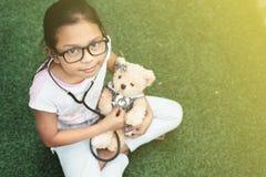 Молодой маленький азиатский играть девушки претендует быть доктором eaxamine маленькой девочки ее плюшевый медвежонок с стетоскоп Стоковая Фотография RF