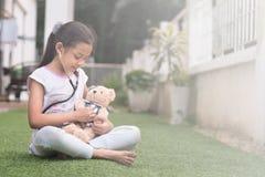 Молодой маленький азиатский играть девушки претендует быть доктором eaxamine маленькой девочки ее плюшевый медвежонок с стетоскоп Стоковое Изображение RF