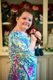 Молодой маленький ирландский рыжий портрет девушки смотря и усмехаясь на камере держа куклу себя которая выглядеть как Стоковые Изображения RF