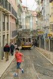 Молодой мальчик бежать перед известным трамваем 28 на Caveleiro стоковое изображение rf
