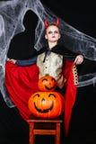 Молодой мальчик в костюме дьявола хеллоуина при тыквы имея потеху на черной предпосылке с паутиной Стоковое Изображение