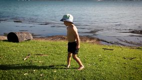 """Молодой мальчик в шортах и шляпа ведра на травянистом береге лета озера на высоте в показывая его версию как сделать """"Flo видеоматериал"""