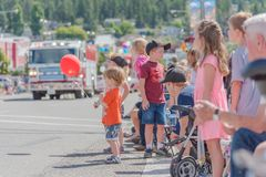Молодой мальчик держа красный воздушный шар при дети и родителей наблюдая парад стоковые фотографии rf
