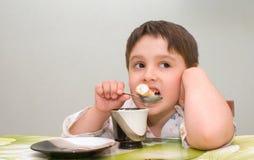 Молодой мальчик есть еду на таблице Стоковая Фотография