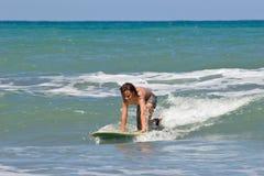 Молодой мальчик занимаясь серфингом в море Стоковое Изображение
