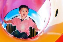 Молодой мальчик играя в скольжении пробки Стоковые Изображения