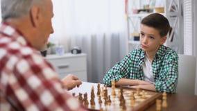 Молодой мальчик играя шахматы с дедом, традиции семьи, развитие разума видеоматериал
