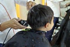 Молодой мальчик имея стрижку стоковое фото rf