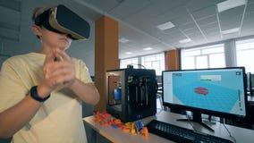 Молодой мальчик используя шлемофон виртуальной реальности для проектировать часть робота напечатал на принтере 3D