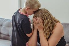 Молодой мальчик, который относят для его матери и полагаться в ее утешая ее по мере того как она плачет стоковые изображения