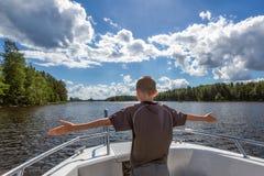 Молодой мальчик наслаждается отключением на моторной лодке стоковые фотографии rf