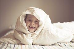 Молодой мальчик на кровати Стоковая Фотография