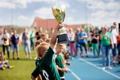 Молодой мальчик поднимая золотую чашку футбола Выигрывая футбольная команда молодости празднуя успех стоковые изображения