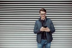 Молодой мальчик просматривает интернет на smartphone и слушает к музыке с наушниками Стоковые Фотографии RF
