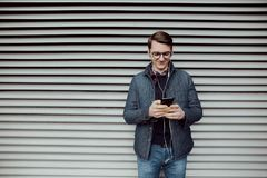 Молодой мальчик просматривает интернет на smartphone и слушает к музыке с наушниками Стоковые Изображения