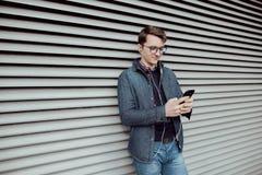 Молодой мальчик просматривает интернет на smartphone и слушает к музыке с наушниками Стоковое Фото