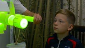 Молодой мальчик проходя обработку в современной клинике вдыхание лазера светлая обработка вдыхания горла УЛЬТРАФИОЛЕТОВАЯ стоковое фото rf