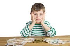 Молодой мальчик сидит перед деньгами Стоковые Изображения RF