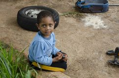 Молодой мальчик сидит стойка на снаружи стены стоковая фотография rf