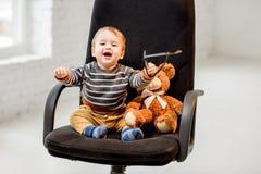 Молодой мальчик сидя на стуле офиса стоковое фото