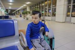 Молодой мальчик сидя самостоятельно в коридоре авиапорта на чувствовать унылое настроение Стоковые Изображения RF
