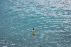 Молодой мальчик скачет в голубое море Стоковые Фото
