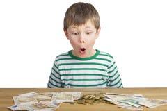 Молодой мальчик смотрит много деньги Стоковые Изображения
