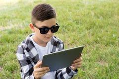 Молодой мальчик с современным прибором стоковая фотография