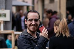 Молодой мальчик с улыбками серег пока выпивающ кофе на улице стоковое фото rf