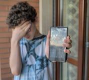 Молодой мальчик, унылый и отчаянный для его smartphone Стоковое Изображение