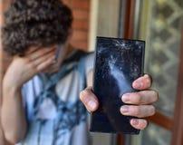Молодой мальчик, унылый и отчаянный для его smartphone Стоковые Изображения RF