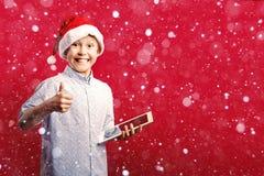 Молодой мальчик santa делая одобренные большие пальцы руки вверх показывать пока держащ таблетку Стоковые Фото