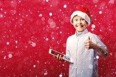 Молодой мальчик santa делая одобренные большие пальцы руки вверх показывать пока держащ таблетку Стоковые Фотографии RF