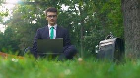 Молодой менеджер работая на ноутбуке в лесе, наслаждаясь природой, избежание от офиса сток-видео