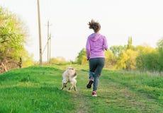 Молодой милый бежать девушки внешний весной с собакой Стоковые Фото